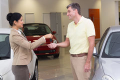 Smiling businesswoman giving car key to happy customer. At new car showroom Stock Images