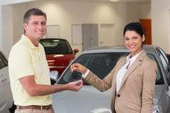 Smiling businesswoman giving car key to happy customer. At new car showroom Stock Photography