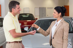 Smiling businesswoman giving car key to happy customer. At new car showroom Stock Image