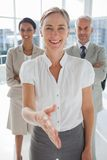 Smiling businesswoman giving a handshake with colleagues behind Royalty Free Stock Photography