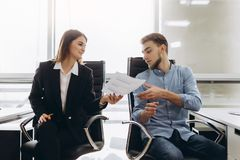 Smiling businesswoman giving papers to someone in office stock image