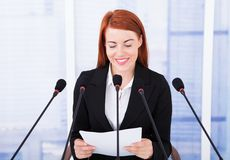 Smiling businesswoman giving speech at conference Royalty Free Stock Photography