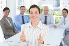 Smiling businesswoman giving thumbs up with her team behind Royalty Free Stock Photo