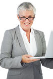 Smiling businesswoman with glasses holding her laptop Stock Image