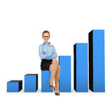 Smiling businesswoman in glasses sitting on chart Royalty Free Stock Photos
