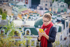 Smiling businesswoman in glasses using smartphone in city Royalty Free Stock Images