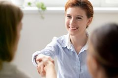Smiling businesswoman greeting shaking hand client, new colleague, vacancy candidate royalty free stock photos