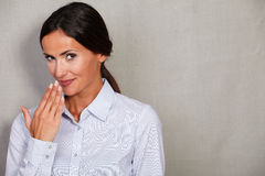 Smiling businesswoman with hand to mouth Stock Photo