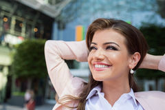 Smiling businesswoman with hands on head against modern building. Close up of smiling elegant businesswoman with hands on head in pink jacket and white shirt stock photography