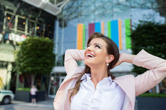 Smiling businesswoman with hands on head against modern building. Close up of smiling elegant businesswoman with hands on head in pink jacket and white shirt stock image