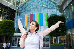 Smiling businesswoman with hands up against modern building. Close up of smiling elegant businesswoman with hands up in pink jacket and white shirt against royalty free stock images