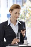 Smiling businesswoman having coffee-break. Smiling businesswoman using mobilephone having coffee-break, looking at camera Royalty Free Stock Photo