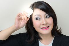 Smiling businesswoman having an idea with bright light bulb. Over her head Royalty Free Stock Image