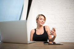 Smiling businesswoman having on-line video call on cell telephone. Cheerful female publication specialist reading private information on mobile phone, sitting at Royalty Free Stock Photos