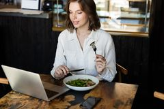 Smiling businesswoman having lucnch at the cafe indoors stock images