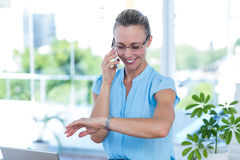 Smiling businesswoman having a phone call and checking time Stock Image