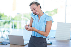 Smiling businesswoman having a phone call and taking notes Stock Photos