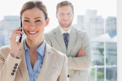 Smiling businesswoman having phone conversation. With coworker behind her Royalty Free Stock Image