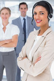 Smiling businesswoman with headset crossing her arms Royalty Free Stock Images