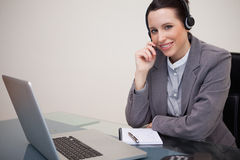 Smiling businesswoman with headset on her laptop Stock Photo