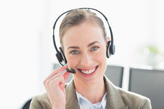 Smiling businesswoman with headset looking at camera Royalty Free Stock Photo