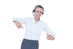 Smiling businesswoman with headset pointing Royalty Free Stock Photo