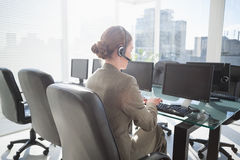 Smiling businesswoman with headset using computers Stock Photo