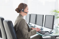 Smiling businesswoman with headset using computers Royalty Free Stock Images