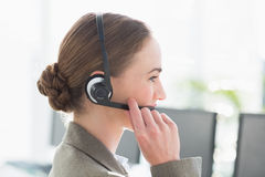 Smiling businesswoman with headset using computers Stock Image
