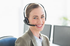 Smiling businesswoman with headset using computers Stock Photography