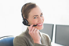 Smiling businesswoman with headset using computers Royalty Free Stock Photo