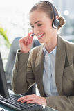 Smiling businesswoman with headset using computers Stock Photos