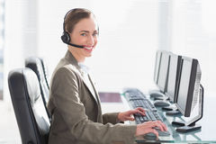 Smiling businesswoman with headset using computers Royalty Free Stock Photography