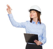 Smiling businesswoman in helmet with clipboard Royalty Free Stock Image