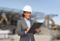 Smiling businesswoman in helmet with clipboard Stock Photos