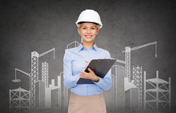 Smiling businesswoman in helmet with clipboard Stock Photography