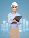 Smiling businesswoman in helmet with clipboard Royalty Free Stock Photos