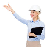 Smiling businesswoman in helmet with clipboard Royalty Free Stock Photography