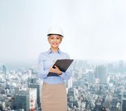 Smiling businesswoman in helmet with clipboard Stock Photo