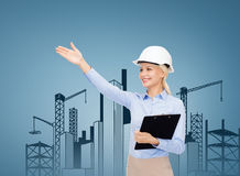 Smiling businesswoman in helmet with clipboard Stock Image