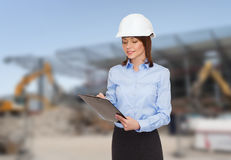 Smiling businesswoman in helmet with clipboard Royalty Free Stock Images