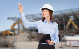 Smiling businesswoman in helmet with clipboard Royalty Free Stock Photo