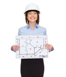 Smiling businesswoman in helmet showing blueprint Stock Photo