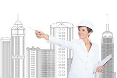 Smiling businesswoman in helmet studying the sketch of future business centre. Royalty Free Stock Image