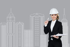 Smiling businesswoman in helmet studying the sketch of future business centre. Stock Images