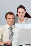 Smiling businesswoman helping her colleague Royalty Free Stock Photos