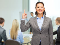 Smiling businesswoman with her finger up at office Stock Image
