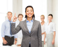 Smiling businesswoman with her finger up at office Stock Photography