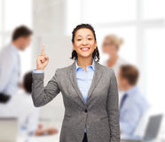 Smiling businesswoman with her finger up at office Stock Images