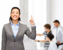 Smiling businesswoman with her finger up at office Stock Photos